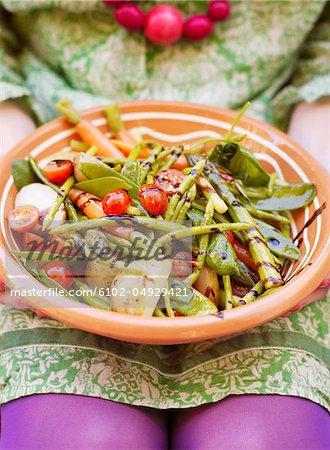 Frau hält Teller mit Gemüsesalat