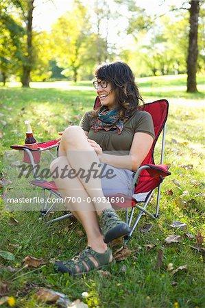 Femme assise sur une chaise de jardin