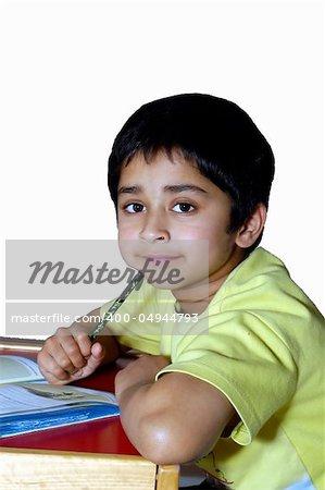 A kindergarden kid doing homework agains a white background