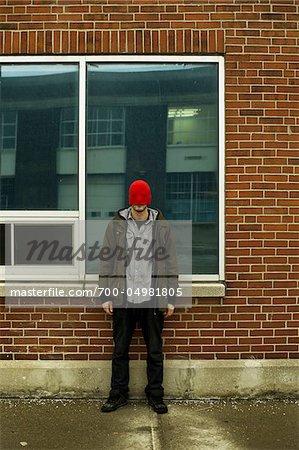 Homme avec chapeau tiré sur Face debout en face de bâtiment