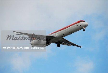 Modern jet airplane descending for landing