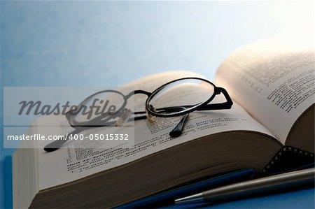 Livre avec des lunettes et stylo