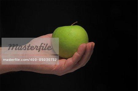A person holding a Granny Smith apple.
