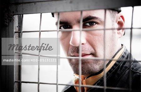 Man Close - Up Portrait. Behind An Iron Lattice