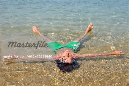 Garçon flottant dans l'eau, Corse, France