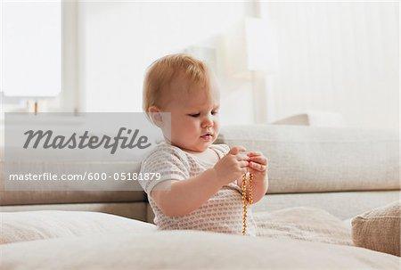 Baby-Mädchen spielen mit Perlen