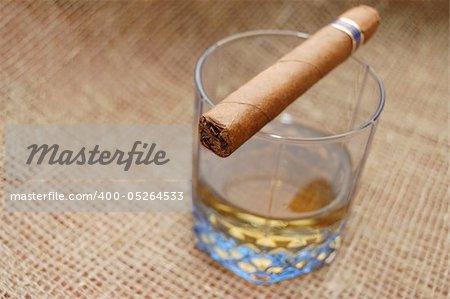 Cuban cigar on glass with wiskey