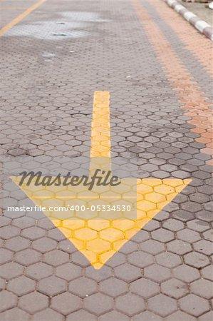 yellow arrow on the ground, arrow near sidewalk in tha park