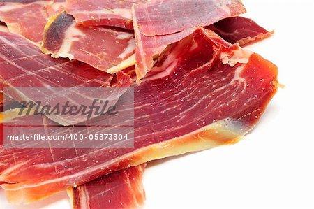 some slices of spanish serrano ham on a white background