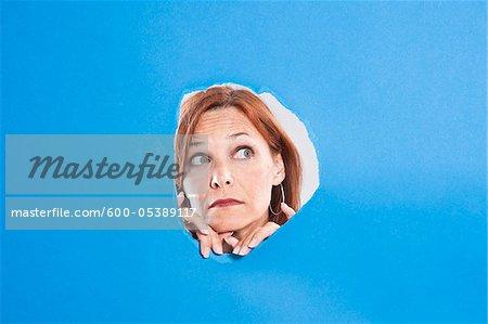 Femme regardant à travers le trou