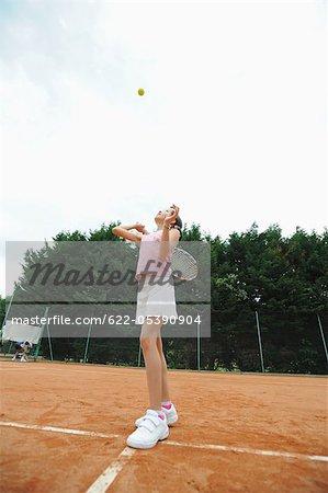 Girl Serving The Tennis Ball