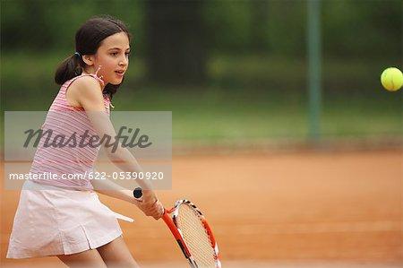 Caucasian Girl Hitting Tennis Ball