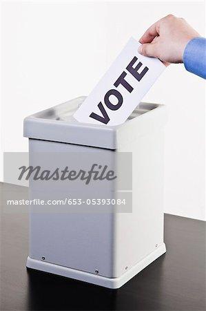 Un homme mettre un bulletin de vote avec le mot VOTE écrit à ce sujet dans une urne, détail mains