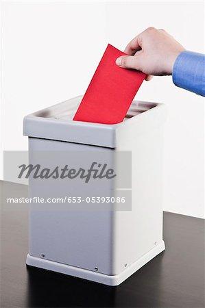 Un homme mettre un bulletin de vote blanc rouge dans une urne, détail mains