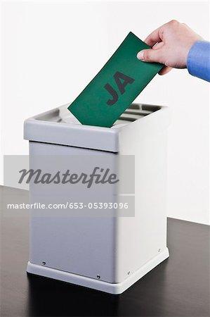 Un homme mettre un bulletin de vote avec le mot JA écrit à ce sujet dans une urne, les mains en gros plan