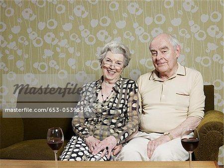 Mari et femme détendue sur le canapé, avec deux verres de vin rouge sur la table à l'avant