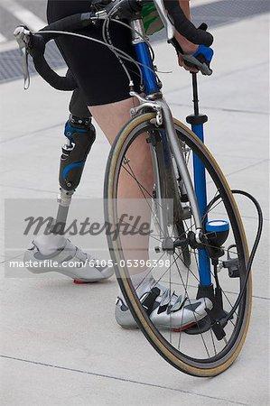 Femme avec une jambe artificielle, pompage de l'air dans une bicyclette