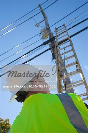 Ingénieur placer une échelle pour grimper le poteau électrique