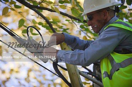 Ingénieur installation du filtre de canal à une boîte de distribution de câble sur un poteau électrique