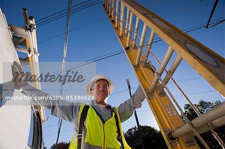 Ingénieur détenant une échelle à l'emplacement de la ligne électrique
