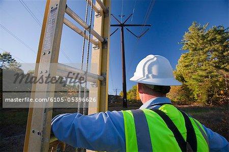 Ingénieur échelle d'installer l'équipement sur les poteaux d'électricité