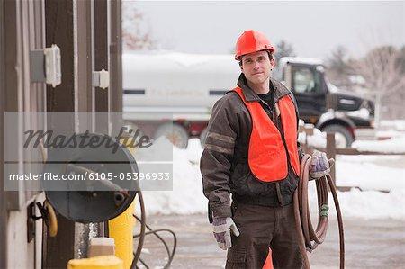 Transportation engineer unrolling hose at an industrial garage