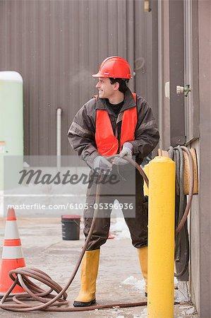 Transportation engineer reeling a hose at industrial garage
