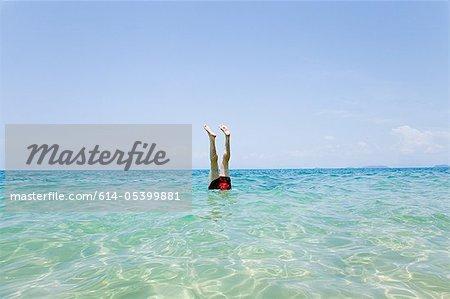 Nageur avec jambes qui sort de l'eau des Penhentian Kecil, îles Perhentian en Malaisie