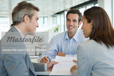 Paar diskutieren Vertrag beim Treffen mit Kaufmann
