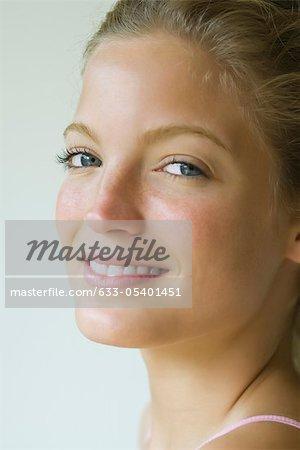Jeune femme regardant par-dessus l'épaule à la caméra, portrait