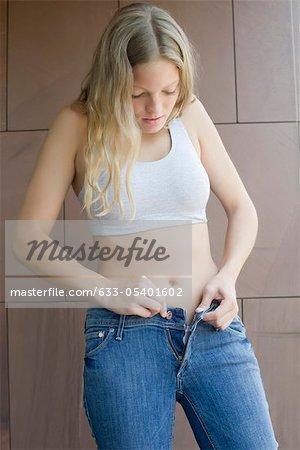 Jeune femme à boutonnage jeans serrés