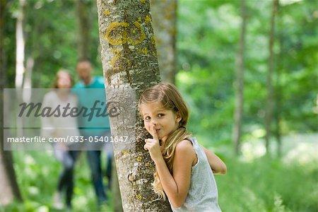 Jeune fille se cachant derrière l'arbre avec le doigt sur les lèvres