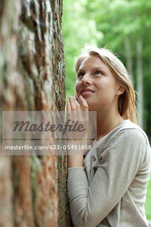 Femme s'appuyant sur l'arbre, en levant