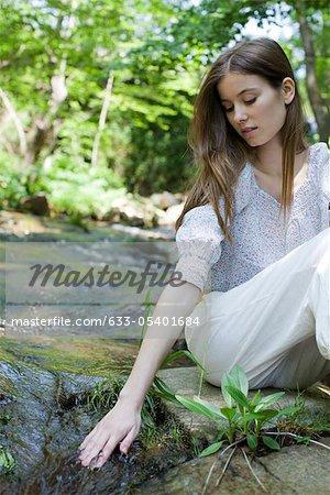 Jeune femme touchant les cours d'eau