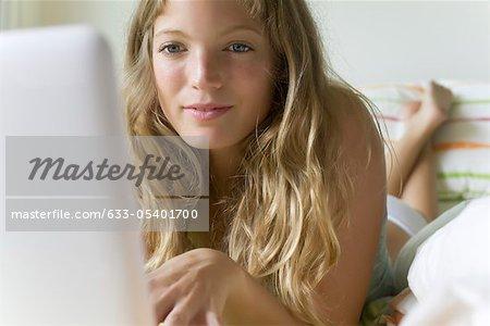 Jeune femme au lit, à l'aide d'ordinateur laZSop
