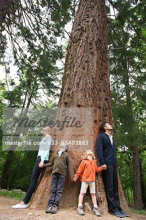 Famille debout ensemble à la base du grand arbre, main dans la main