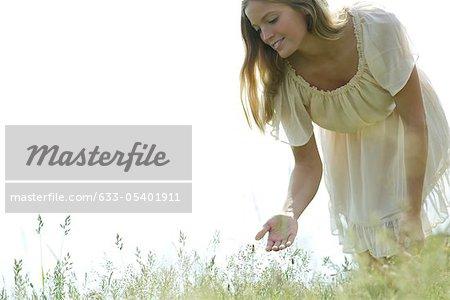 Jeune femme de flexion plus toucher les herbes hautes