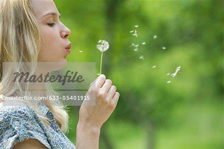Junge Frau bläst Löwenzahn Blume