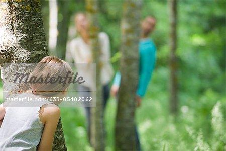 Jeune fille se cachant derrière l'arbre