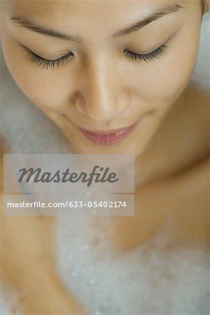 Jeune femme prenant le bain à bulles, vue grand angle