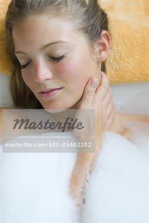 Jeune femme se détendre dans le bain à bulles