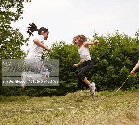 Jeunes filles sautant par-dessus une corde