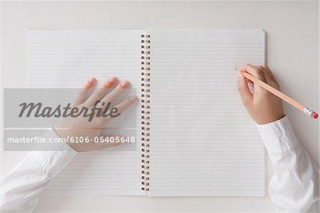 Main de l'enfant qui tente d'écrire dans la note