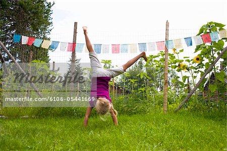 Girl doing cartwheel in backyard.