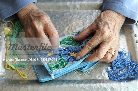Femme senior à l'aide d'aiguilles pour tapisserie à l'aiguille