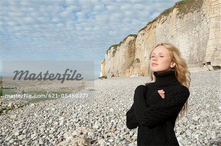 Portrait de jeune femme avec les bras croisés sur la plage