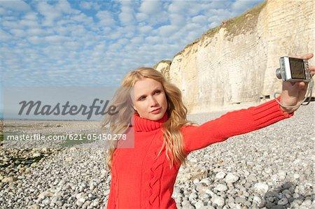 Femme de prendre une photo d'elle-même sur la plage
