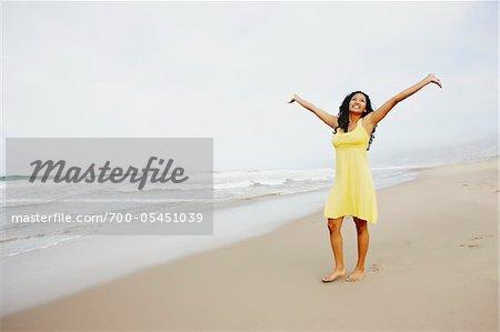 Frau am Strand mit offenen Armen