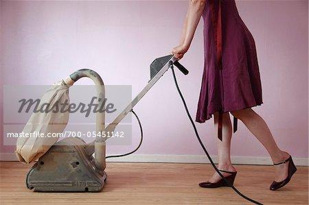 Woman Wearing Dress Using Electric Sander on Hardwood Floor