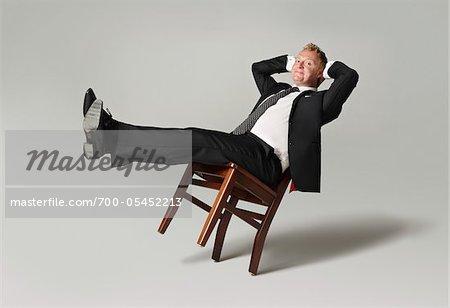 Homme d'affaires s'appuyant sur chaise